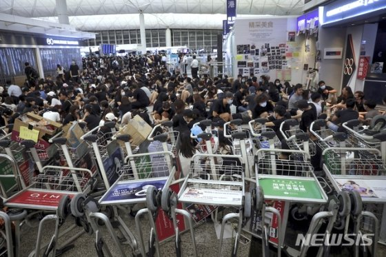 지난 13일 오후 홍콩의 '범죄인 인도 법안(송환법)' 반대 시위대가 공항 내 카트를 쌓아 차벽을 이루며 대규모의 농성을 벌이고 있다. 지난 이틀 동안 탑승 수속이 중단됐던 홍콩국제공항은 14일(현지시간) 오전 업무를 재개한 상황이다. / 홍콩=AP/뉴시스