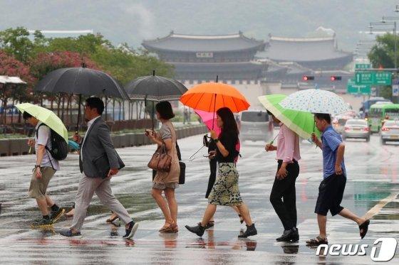 지난 12일 오전 서울 종로구 광화문네거리에서 우산을 쓴 시민들이 출근길 발걸음을 재촉하고 있다./사진=뉴스1