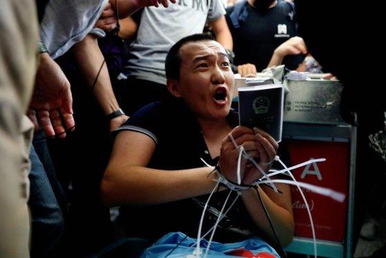 13일 밤 홍콩국제공항에서 시위대에 에워쌓인 중국 환구시보 기자 후궈하오가 손발이 묶인 채 호소하고 있다. /사진=로이터