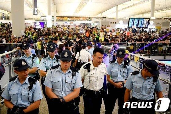 13일 (현지시간) 송환법에 반대하는 시위대가 점거하고 있는 홍콩 국제공항 입구에 경찰이 경비를 서고 있다. © AFP=뉴스1