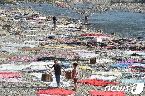 태풍 레끼마가 지나간 중국 저장성 타이저우 마을의 강둑에 주민들이 담요와 옷가지를 말리기 위해 펼쳐놓고 있다. © 로이터=뉴스1 © News1 우동명 기자