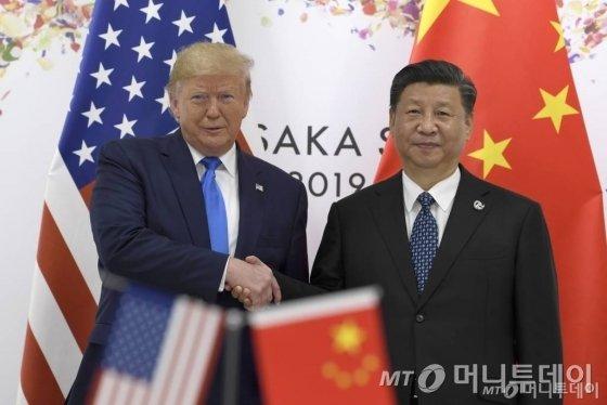【오사카(일본)=AP/뉴시스】도널드 트럼프 미 대통령(왼쪽)과 시진핑(習近平) 중국 국가주석이 29일 주요 20개국(G20) 정상회담이 열리고 있는 일본 오사카(大阪)에서 정상회담을 위해 만나 악수를 나누고 있다. 2019.6.29