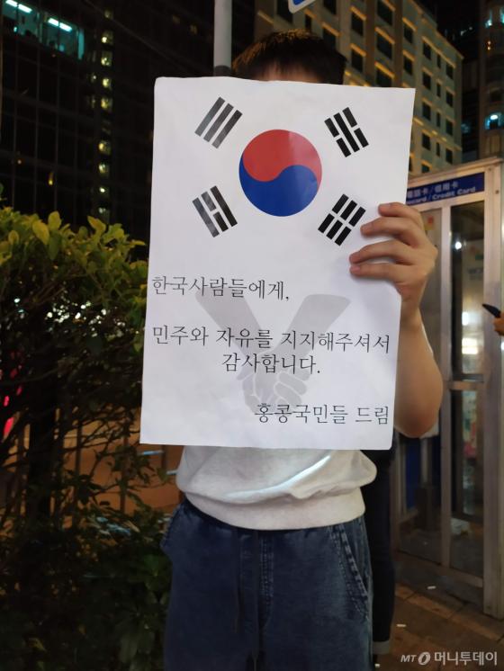 지난 23일(현지시간) 밤 홍콩 도심서 열린 '인간 띠' 시위에 참가한 한 남성이 태극기와 시위를 지지해준 한국인에게 감사하다는 내용의 문구가 새겨진 종이를 들고 있다. /사진=유희석 기자