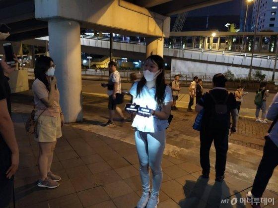 23일 홍콩에서 한 여성이 '일국양제를 지켜달라'는 메시지를 들고 시위를 하고 있다. / 사진=유희석