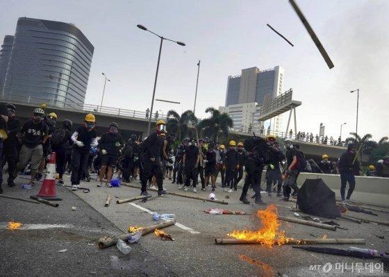 【홍콩=AP/뉴시스】24일(현지시간) 홍콩 거리에서 시위대가 시위 중 경찰과 충돌하고 있다.    시위대는 쿤통 등지에서 바리케이드를 치고 경찰과 대치했고, 경찰은 시위대를 향해 최루탄을 쏘며 진압을 시도했다.  홍콩 중고생들은 정부가 시위대의 요구 조건을 수용하지 않을 경우 2주 동안 수업을 거부한다고 밝혔다. 2019.08.24.