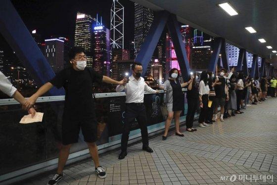 【홍콩=AP/뉴시스】23일(현지시간) 홍콩 거리에서 송환법 반대 시위대가 손을 잡고 한 줄로 서서 인간 띠 시위를 벌이고 있다.    시위대는 1989년 8월 23일 발트 3국의 국민이 손을 맞잡고 670km에 이르는 '발트의 길'을 만들어 소련에 저항한 역사적 사건에 영감을 받아 시내와 항구 등에서 60km에 달하는 인간 띠를 형성해 이른바 '홍콩의 길' 시위를 벌였다. 2019.08.24.