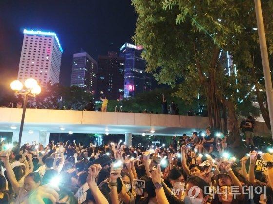 지난 23일(현지시간) 밤 거대한 인간 띠 잇기 시위에 참여한 홍콩 시민들이 각자 손전등 기능을 킨 스마트폰을 높이 들고 중국과의 '범죄인 인도 협정' 체결 계획 폐기 등으로 요구하고 있다. /사진=유희석 기자