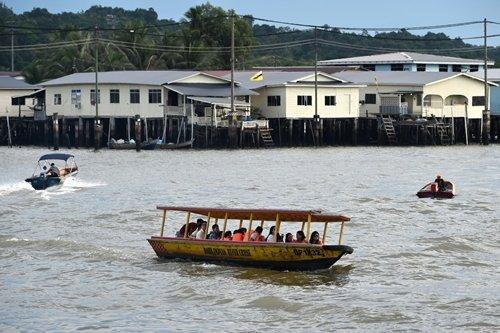 관광객들이 보트를 타고 캄퐁 아에르(Kampong Ayer·브루나이 강 위에 지어진 수상 가옥촌) 근처를 구경하고 있다. /사진=AFP