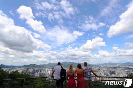 지난 7월 서울 남산을 찾은 외국인 관광객이 맑고 청명한 하늘과 서울시내를 바라보고 있다. /사진=뉴스1