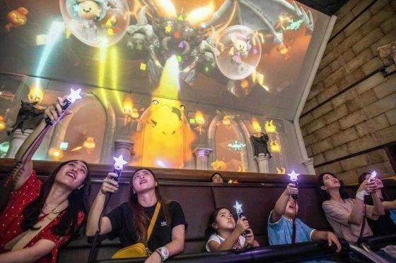 에버랜드가 국내 IT 강소기업들과 손잡고 개발한 '레니의 마법학교'를 찾은 고객들이 가상의 드래곤을 마법봉으로 물리치고 있다. /사진=에버랜드