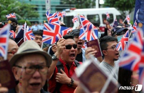 홍콩인들이 영국 영사관 앞으로 몰려가 유니언잭을 흔들며 홍콩인의 영국 영주를 허용하라고 요구하고 있다. © AFP=뉴스1