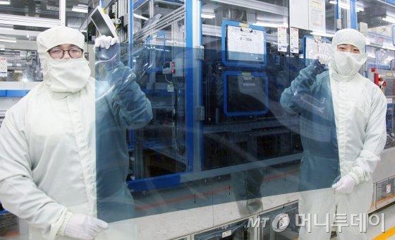 경기도 파주 LG디스플레이 공장에서 연구원들이 나노셀 TV에 적용되는 편광판을 들고 있다/사진제공=LG디스플레이