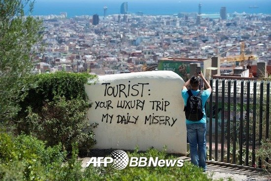 """2017년 8월10일 스페인 바르셀로나에서 찍힌 사진. 바르셀로나시가 내려다보이는 위치 한 벽면에 """"관광객 여러분, 당신의 호화스런 여행은 내 일상의 고통입니다""""라는 글귀가 적혀있다. /AFPBBNews=뉴스1"""