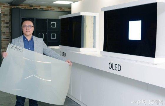 17일 서울 여의도 LG트윈타워에서 열린 LG전자 디스플레이 기술설명회에서 LG전자 HE연구소장 남호준 전무가 패널의 차이를 설명하기 위해 국내시장에 판매중인 QLED TV에 적용된 퀀텀닷 시트를 들고 있다. /사진=LG전자 제공