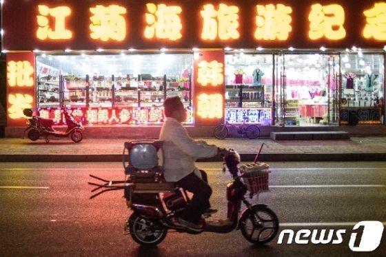 북한 상품을 판매하는 중국 랴오닝성 단둥 시내의 기념품점 앞을 한 남성이 스쿠터를 타고 지나가고 있다. © AFP=뉴스1