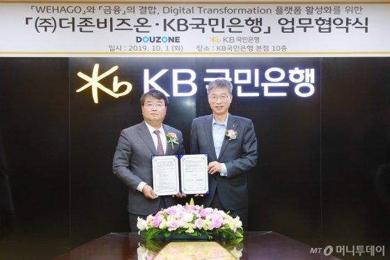 김용우 더존비즈온 대표(왼쪽)와 허인 KB국민은행장이 업무협약서를 교환하고 있다/사진제공=더존비즈온