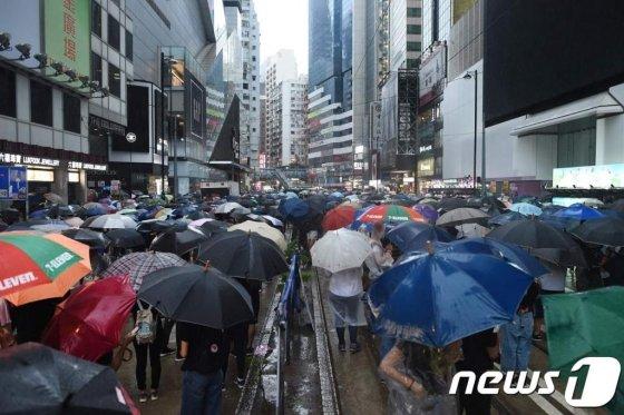 지난 6일(현지시간) 홍콩 정부의 '복면금지법' 시행에 반대하는 시위대가 빗속 우산을 쓰고 행진을 하고 있다. /사진=뉴스1