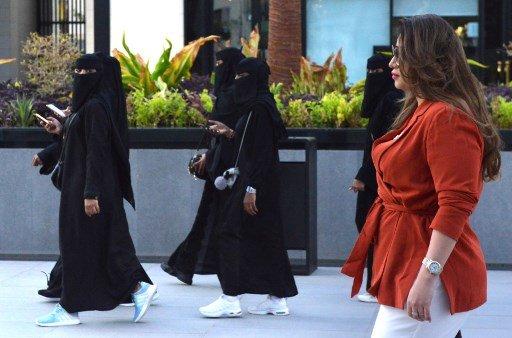 한 외국인 여성이 아바야를 입은 사우디 여성들 옆을 지나가고 있다. /사진=AFP