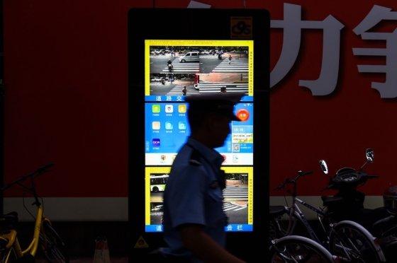 교통법규 단속을 명분으로 중국 상하이의 한 도로에 설치된 안면인식 시스템 앞을 교통경찰이 지나고 있다. /사진=AFP
