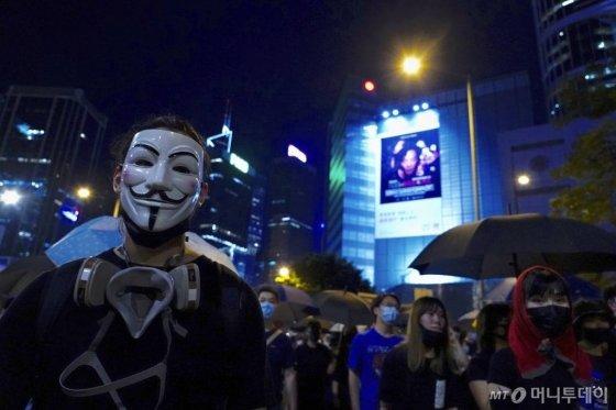 4일 홍콩 도심에서 한 시위자가 '가이 포크스' 가면을 쓰고 거리 시위에 동참하고 있다. 앞서 이날 오후 홍콩 정부는 시위대의 마스크 착용을 금지하는 '복면금지법'을 5일 0시부터 시행하기로 했다. / 사진=뉴시스(AP)