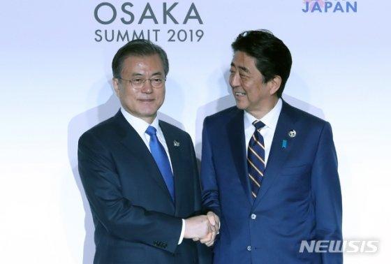 문재인 대통령 지난 6월28일 일본 오사카 국제컨벤션센터 인텍스오사카에서 열린 G20 정상회의 공식환영식에서 아베 신조 일본 총리와 악수하고 있다. /뉴시스