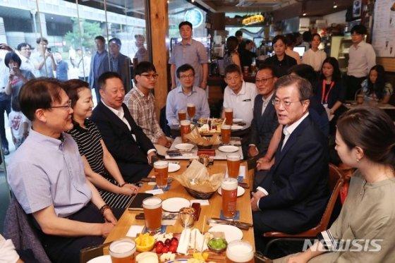 문재인 대통령이 18년 7월 26일 오후 서울 광화문 인근 호프집을 방문해 '퇴근길 국민과의 대화 일환'으로 참석자들과 맥주를 마시며 대화하고 있다. / 사진 = 뉴시스
