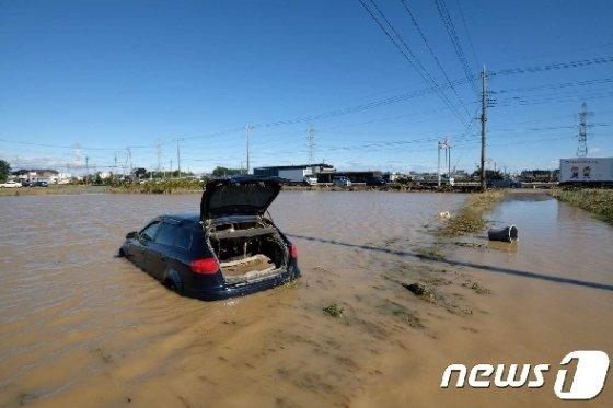 12일 제19호 태풍 하기비스의 영향으로 폭우가 쏟아진 일본 사이타마현 히가시 마쓰야마에서 차량 한 대가 물에 잠겨 있다. © AFP=뉴스1