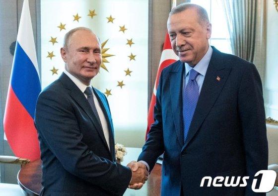 블라디미르 푸틴 러시아 대통령이 지난달 16일(현지시간) 앙카라에서 시리아 내전 종식을 위한 '러시아-터키-이란' 3자회담 중 레제프 타이이프 에르도안 터키 대통령과 악수를 하고 있다./로이터=뉴스1