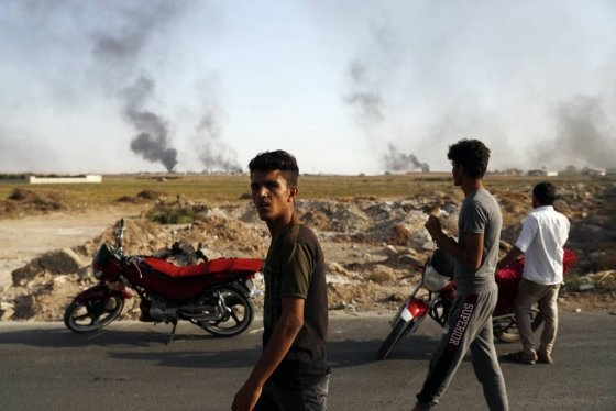 """10일(현지시간) 터키-시리아 국경지대의 악카칼레 지역 주민들이 터키군 폭격으로 시리아 지역에서 연기가 피어오르는 모습을 지켜보고 있다.   앞서 메블뤼트 차우쇼을루 터키 외무 장관은 """"터키군이 시리아 북부 깊숙한 30㎞까지 진격할 것""""이라며 """"모든 테러리스트가 무력화될 때까지 작전은 이어질 것""""이라고 말했다. /AP=뉴시스"""