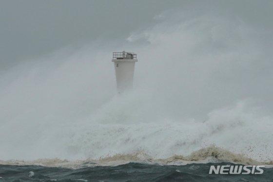 12일 일본 미에현 키호 소재 한 항구에서 19호 태풍 하기비스로 인해 파도가 크게 일면서 방파제와 등대를 덮이고 있다. 2019.10.12./사진=뉴시스