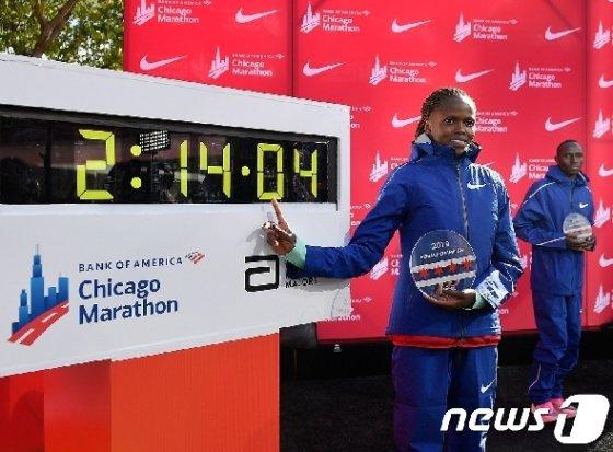 13일(현지시간) 2019 시카고 마라톤 대회에서 2시간14분4초 기록으로 세계기록을 다시 쓴 브리지드 코스게이(케냐)가 기록 전광판 앞에서 포즈를 취하고 있다. © AFP=뉴스1