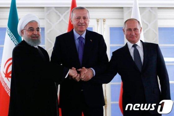 (앙카라 AFP=뉴스1) 우동명 기자 = 블라디미르 푸틴 러시아 대통령과 레제프 타이이프 에르도안 터키 대통령, 하산 로하니 이란 대통령이 지난달 16일(현지시간) 앙카라에서 시리아 내전 종식을 위한 3자회담에 앞서 손을 잡고 있다.   © AFP=뉴스1  <저작권자 © 뉴스1코리아, 무단전재 및 재배포 금지>
