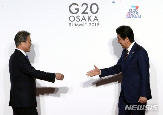 【오사카(일본)=뉴시스】박진희 기자 = 문재인 대통령이 28일 일본 오사카 국제컨벤션센터 인텍스오사카에서 열린 G20 정상회의 공식환영식에서 아베 신조 일본 총리와 악수하고 있다. 2019.06.28.   pak7130@newsis.com
