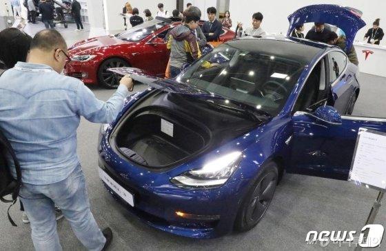 (대구=뉴스1) 공정식 기자 = 17일 대구 북구 엑스코(EXCO)에서 개막한 '대구 국제 미래자동차 엑스포(DIFA) 2019'를 찾은 시민들이 테슬라의 보급형 전기차 '모델 3'를 살펴보고 있다. 2019.10.17/뉴스1  <저작권자 © 뉴스1코리아, 무단전재 및 재배포 금지>