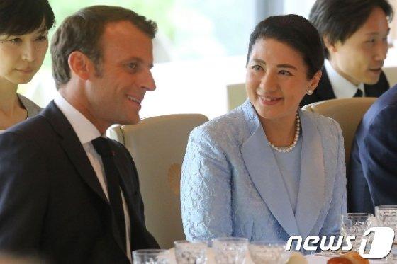 에마뉘엘 마크롱 프랑스 대통령과 통역 없이 대화를 나누는 마사코 왕비. © AFP=뉴스1