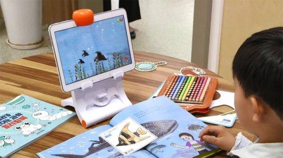 웅진북클럽 회원이 직접 색칠한 물고기를 인터랙티브북 화면에 구현하고 있다. / 사진제공=웅진씽크빅