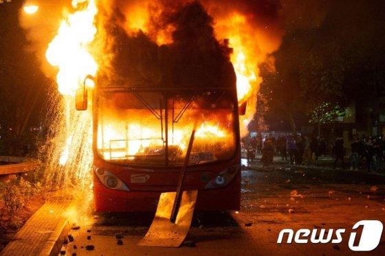 (산티아고 AFP=뉴스1) 우동명 기자 = 20일 (현지시간) 산티아고에서 지하철 요금 인상으로 촉발된 칠레 반정부 시위대의 방화로 버스가 불에 타고 있다.  © AFP=뉴스1  <저작권자