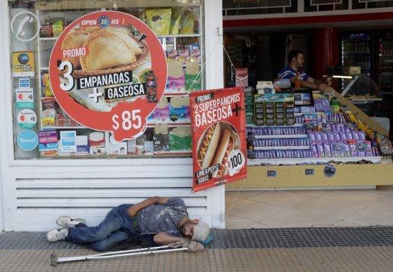 아르헨티나 수도 부에노스아이레스의 상점 앞에 다리를 다친 한 남성이 누워있다/사진=로이터