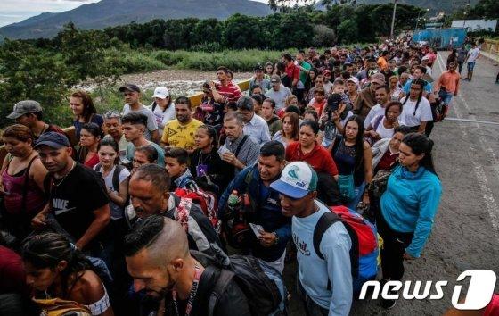 (쿠쿠타 AFP=뉴스1) 우동명 기자 = 지난 6월 9일(현지시간) 베네수엘라인들이 생필품과 약품 등을 구하기 위해 콜롬비아 쿠쿠타에 있는 국경교량인 시몬 볼리바르 다리로 몰려가고 있다. 베네수엘라 정부는 8일 마지막까지 폐쇄했던 콜롬비아 국경 2곳을 4개월만에 열었다.   © AFP=뉴스1