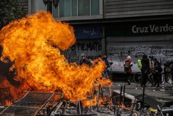 23일(현지시간) 칠레 수도 산티아고에서 시위대가 방화를 벌이는 모습. /사진=AFP<br>