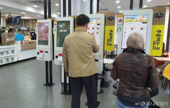 1일 오후 서울 종로구 한 패스트푸드점에서 소비자들이 키오스크를 이용해 주문하고 있다./사진=박가영 기자