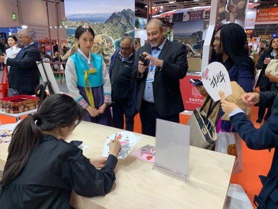 런던 국제관광박람회에서 부채에 한글이름 써주기 체험을 하고 있는 참가자의 모습. /사진=한국관광공사