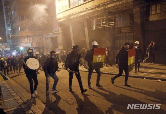 【라파스=AP/뉴시스】5일(현지시간) 볼리비아 수도 라파스에서 에보 모랄레스 대통령의 재선에 반대하는 시위대가 시위 진압 경찰을 향해 움직이고 있다. 반모랄레스 시위대는 에보 모랄레스 대통령이 지난달 20일 치러진 선거에서 부정 당선됐다고 주장하며 시위를 벌이고 있다. 2019.11.06.