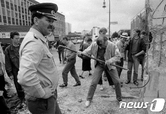 베를린 장벽을 부수는 독일 시민들과 그것을 지켜보는 동독 경찰 <자료 사진> © 로이터=뉴스1