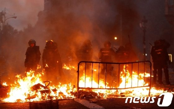 스페인 바르셀로나에서 카탈루냐 총파업 시위가 열린 10월18일(현지시간) 무장 경찰들이 불타는 바리케이드 옆을 지키고 있다.  © 로이터=뉴스1