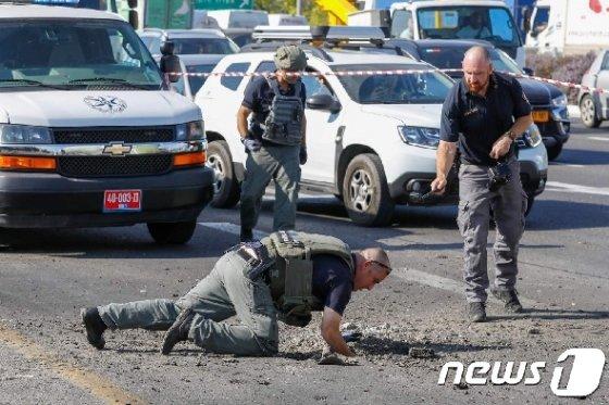 이스라엘 경찰 공병대가 12일(현지시간) 팔레스타인 무장정파 이슬라믹 지하드의 로켓포 공격으로 파손된 남부 아스돗 인근 고속도로 현장을 조사 중이다. © AFP=뉴스1