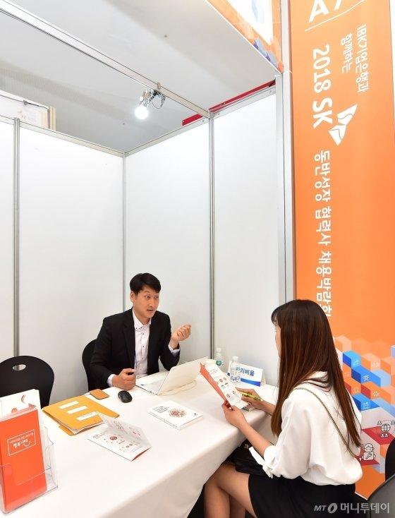 2018년 5월 31일 서울 동대문디자인플라자에서 열린 '2018 SK 동반성장 협력사 채용박람회'에 참여한 구직자가 사회적기업 행복나래 부스에서 채용상담을 받고 있다./사진=SK