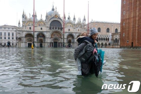 12일(현지시간) 물에 잠긴 이탈리아 북부 베네치아 산마르코 광장을 한 모녀가 걷고 있다. /로이터=뉴스1