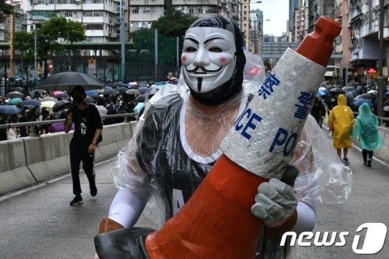 (홍콩 AFP=뉴스1) 우동명 기자 = 6일(현지시간) 홍콩 정부의 '복면금지법' 시행에 반대하는 시위대가 복면을 쓰고 행진에 참여하고 있다.   © AFP=뉴스1  <저작권자 © 뉴스1코리아, 무단전재 및 재배포 금지>