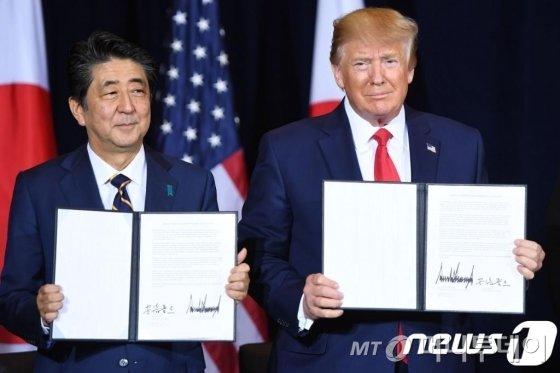 도널드 트럼프 미국 대통령이 지난 9월 25일(현지시간) 뉴욕 유엔본부에서 열린 유엔총회 중 아베 신조 일본 총리와 서명한 무역협정을 들어보이고 있다./AFPBBNews=뉴스1